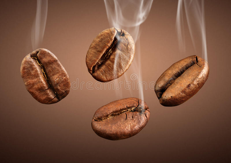 Closeup falling coffee beans with smoke on brown background stock photos