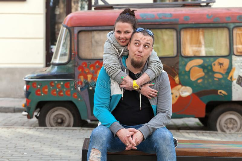 Closeup of family couple near colorful painting old car or gypsy hippie van. Happy romantic young couple in love enjoying in momen royalty free stock images