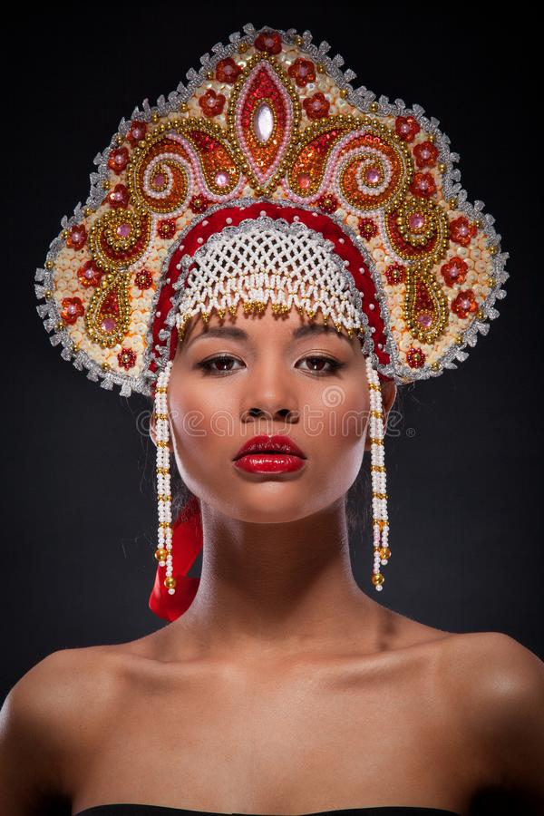 Closeup fashionable portrait of a beautiful african american woman with the richly decorated kokoshnik on her head. Russian style. Fashionable portrait of a stock photo