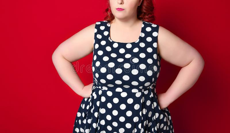 Closeup of a fat angry redhead woman holding her cheek by hand. pinup girl isolated . stock images