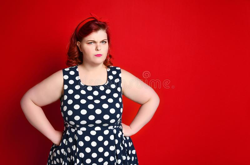 Closeup of a fat angry redhead woman holding her cheek by hand. pinup girl isolated . stock photo