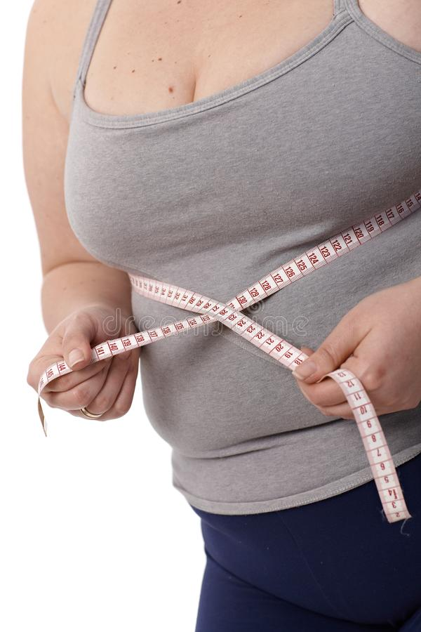 Closeup fat woman measuring waistline. Closeup photo of body of fat woman while measuring waistline by tape measure royalty free stock photos