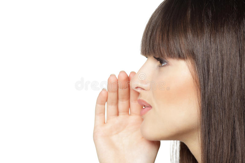 Closeup of female calling out. Side view portrait of young female calling out to someone over white background stock images