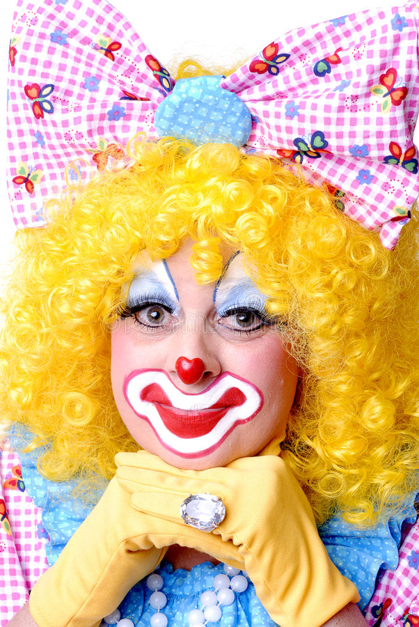 Closeup of Female Clown. With bow in her hair and hands on chin royalty free stock photos