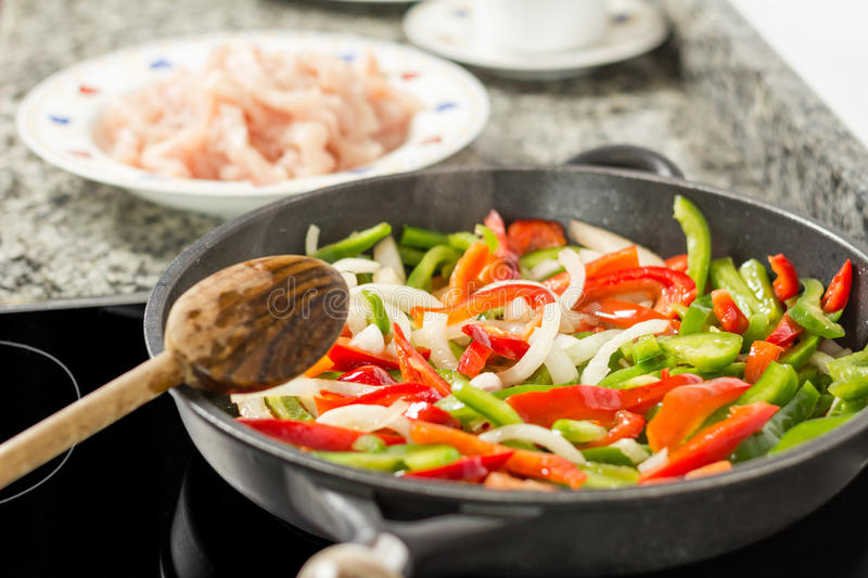 Closeup of female cooking vegetables and chicken in a pan royalty free stock photo