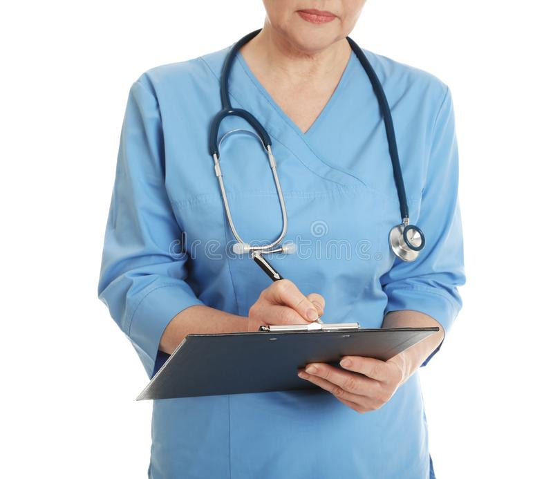 Closeup of female doctor in scrubs with clipboard isolated. Medical staff. Closeup of female doctor in scrubs with clipboard isolated on white. Medical staff royalty free stock photo