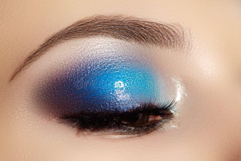 Closeup female eye with beautiful fashion bright make-up. Beautiful shiny blue eyeshadow, wet glitter, black eyeliner royalty free stock photo
