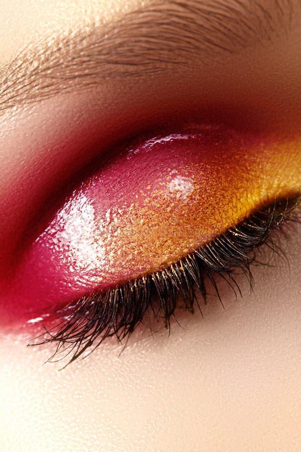 Closeup female eye with beautiful fashion bright make-up. Beautiful shiny gold, pink eyeshadow, wet glitter stock image