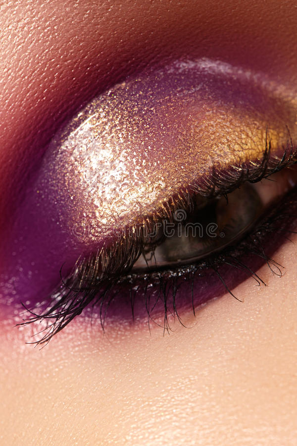 Closeup female eye with beautiful fashion bright make-up. Beautiful shiny gold, purple eyeshadow, wet glitter. Closeup female eye with beautiful fashion bright stock photos
