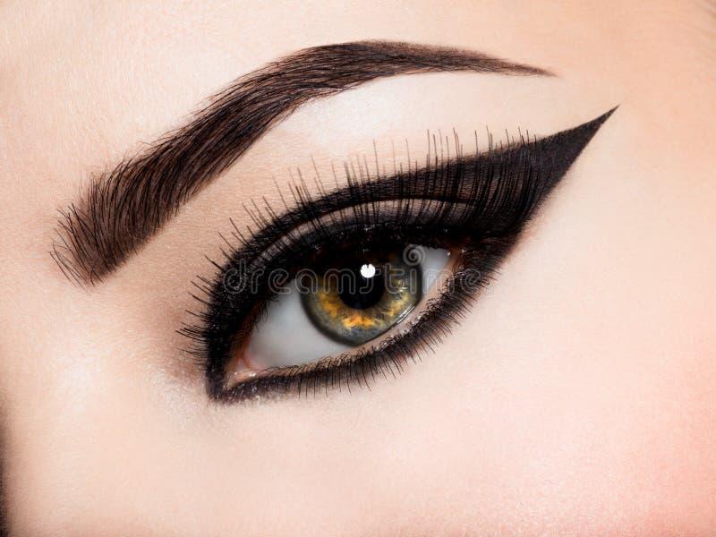 Closeup female eye with creative fashion make-up. brown eyeshadow. Closeup female eye with beautiful fashion bright makeup royalty free stock images