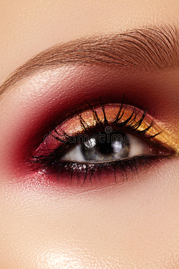 Closeup female eye with fashion bright make-up. Beautiful gold, red eyeshadow, glitter, black eyeliner. Shape Eyebrows. Closeup female eye with fashion bright royalty free stock images