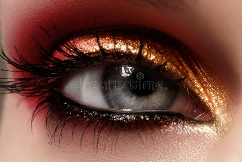 Closeup female eye with fashion bright make-up. Beautiful shiny gold, pink eyeshadow, wet glitter, black eyeliner. Closeup female eye with beautiful fashion stock images