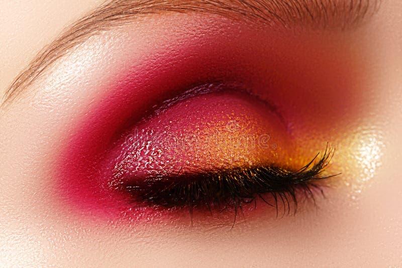 Closeup female eye with fashion bright make-up. Beautiful shiny gold, pink eyeshadow, wet glitter, black eyeliner. Closeup female eye with beautiful fashion royalty free stock photography