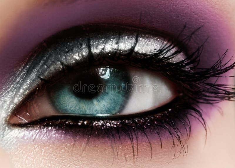 Closeup female eye with fashion bright make-up. Beautiful shiny silver, purple eyeshadow, wet glitter, black eyeliner stock images