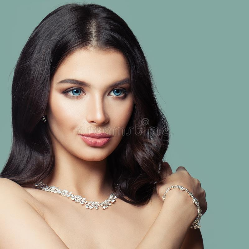 Closeup female face. Brunette woman with makeup, long healthy hairstyle and diamond necklace and bracelet.  stock images