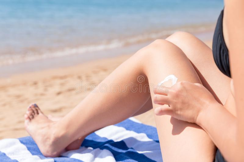 Closeup on female hand applying sunblock on her tanned leg at the beach.  royalty free stock photo