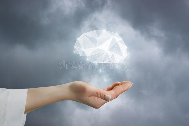 A closeup of female hand with brain model as symbol of mental health. A closeup of female hand with brain model hanging above as psychological symbol of mental royalty free stock photos