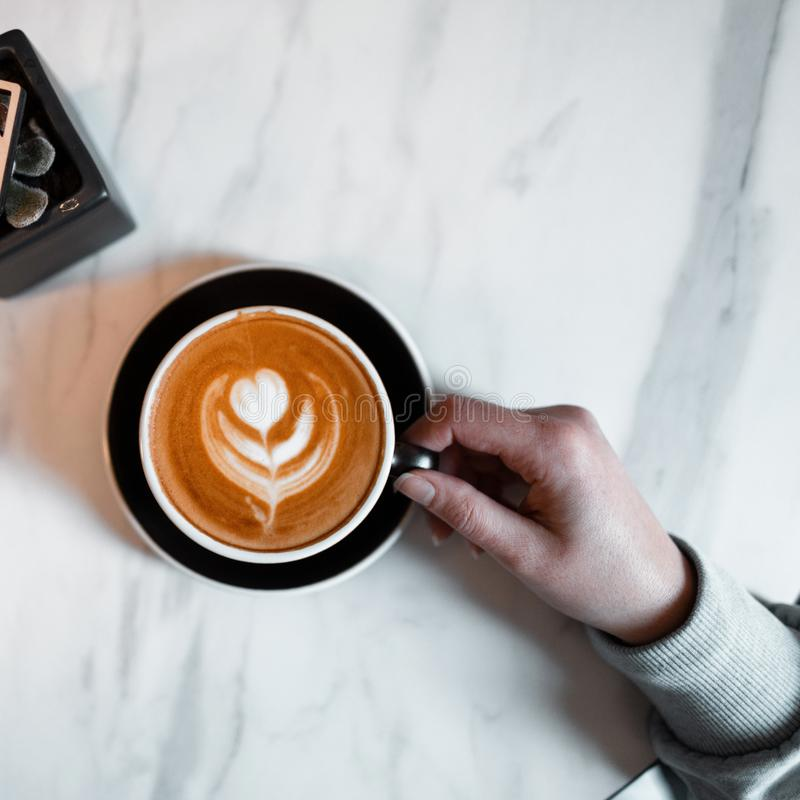 Closeup of female hand holding a cup of cappuccino on a vintage wooden tabletop in a coffee shop. Morning coffee break. View from above stock photos