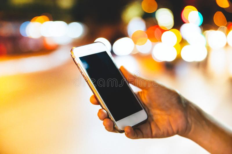 Closeup of female hand holding modern smartphone in the dark. stock photography