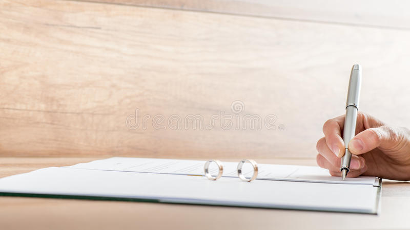 Closeup of female hand signing divorce papers stock image