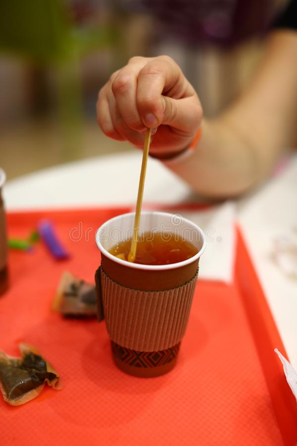 Closeup of female hand stirring black tea in paper cup stock photos