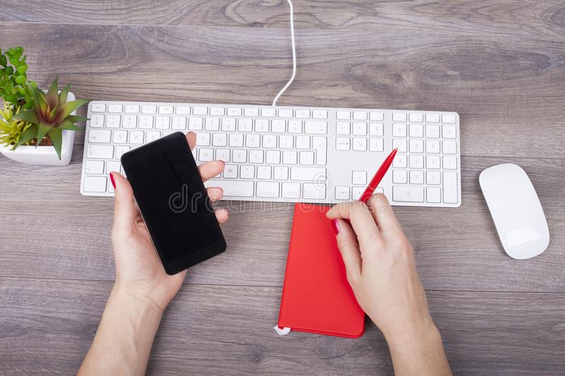 Female hand writing in a notebook and use a mobile phone on the. Closeup of female hand writing in a notebook and use a mobile phone on the desk with a keyboard royalty free stock photography