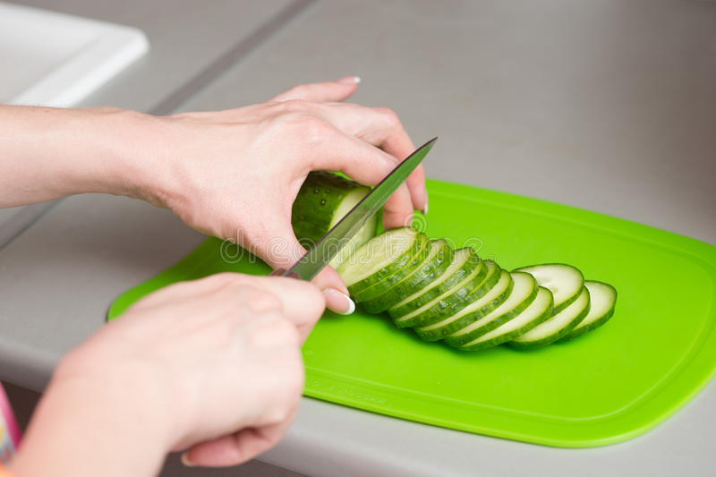 Closeup female hands cutting cucumber royalty free stock photography