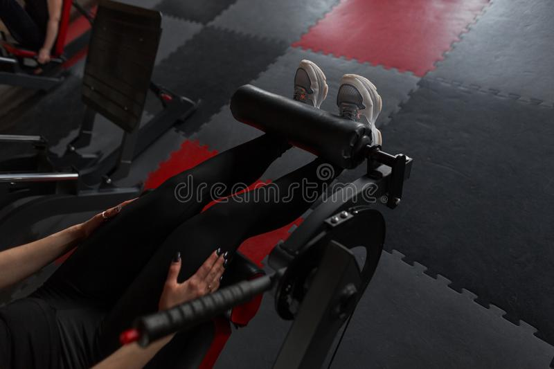 Closeup of female legs in black leggings in white sneakers. Woman do exercises for the legs in the gym. royalty free stock images