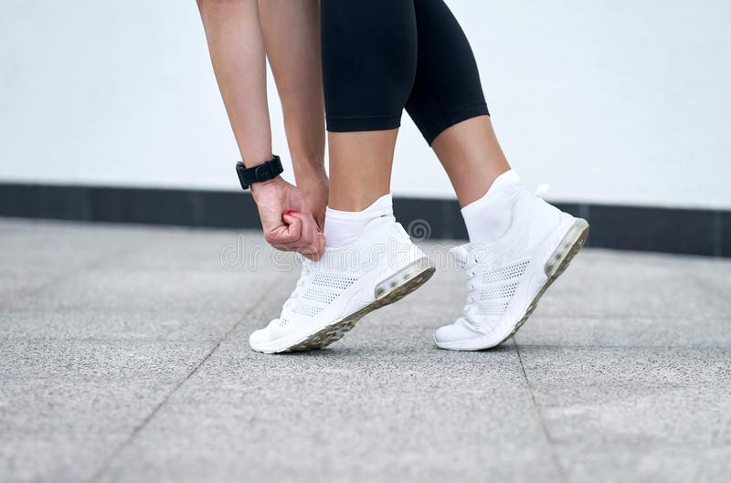 Closeup of female legs in black sport leggings in stylish white sneakers. Active slim woman on a training. Ready to start. Closeup of female legs in black sport royalty free stock photography