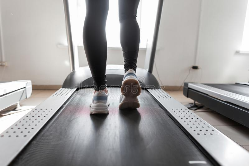 Closeup of female legs. Young woman in black leggings in white sneakers runs on a treadmill at the window in the gym. Girl does cardio workout in a fitness stock photos