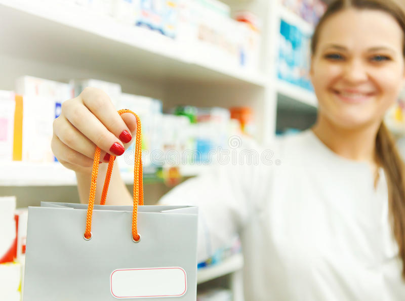 Closeup of a female pharmacist holding packet in her hand at drugstore stock photos