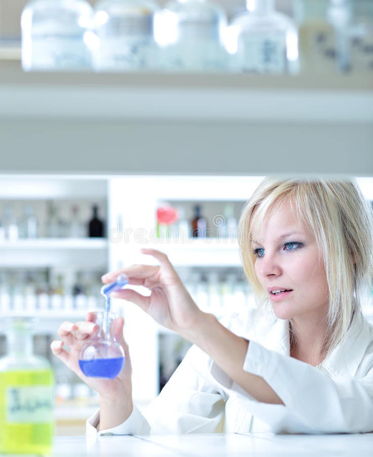 Closeup of a female researcher. Holding up a test tube and a retort and carrying out some experiments stock images