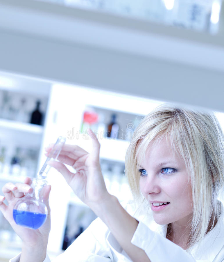 Closeup of a female researcher. Holding a test tube and a retort and carrying out experiments in a laboratory stock photos