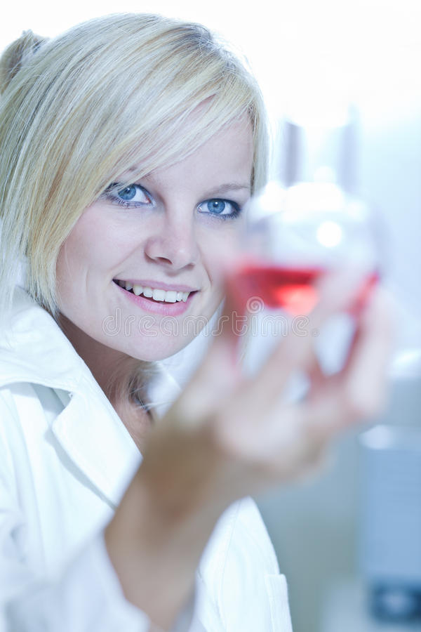Closeup of a female researcher holding a beaker. Carrying out experiments in a chemistry lab royalty free stock photos