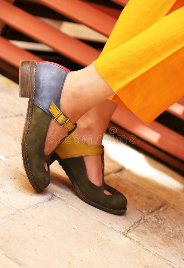 Closeup of female`s feet in classic shoes and yellow elegant dress royalty free stock image