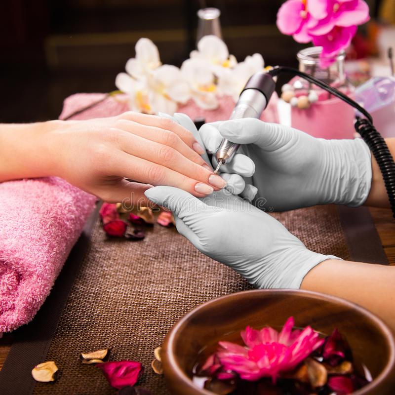 Closeup finger nail care by manicure specialist in beauty salon. stock images
