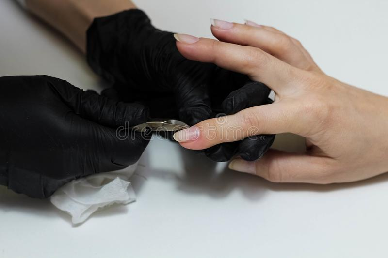 Hands in black gloves cares about hands nails. Manicure beauty salon. Nails filing with file royalty free stock photography