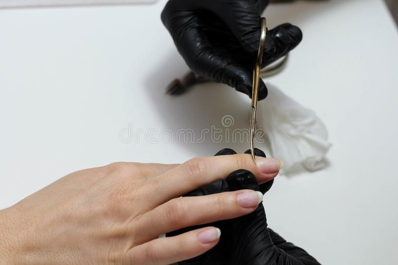 Hands in black gloves cares about hands nails. Manicure beauty salon. Nails filing with file royalty free stock image
