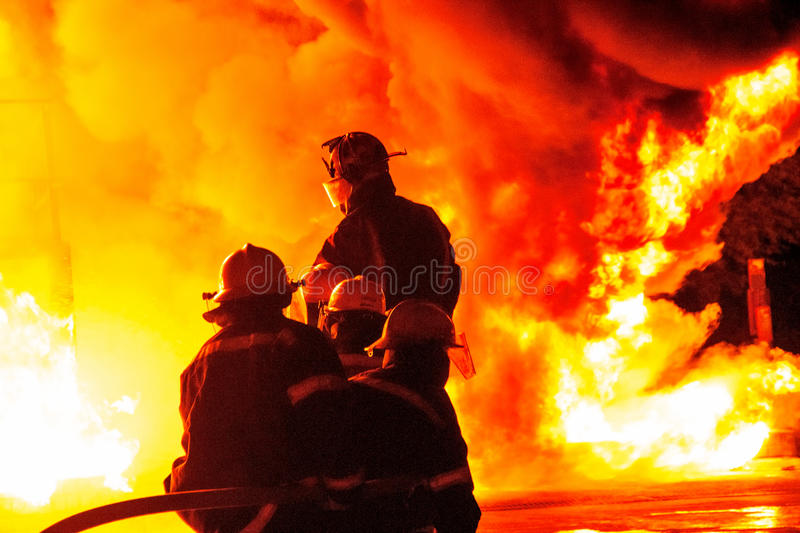 Closeup Firefighters in bunker gear facing white hot inferno with billowing smoke stock photos