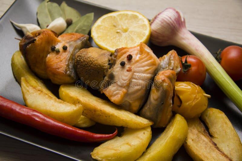 Closeup of fish dish. Fish shishkbob with fried potato and fresh garlic and lemon royalty free stock photography