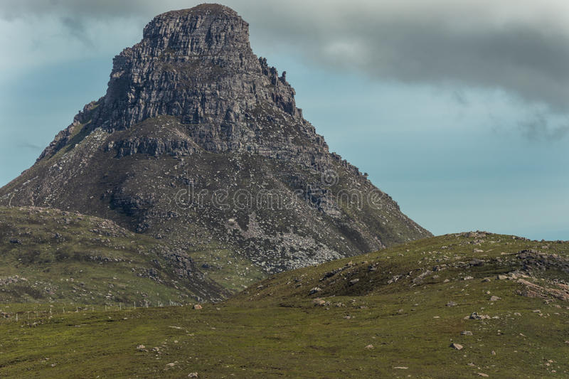 Closeup of flat gray mountain peak, Scotland. Assynt Peninsula, Scotland - June 7, 2012: Closeup of flat gray mountain peak with green hills in front under blue stock image
