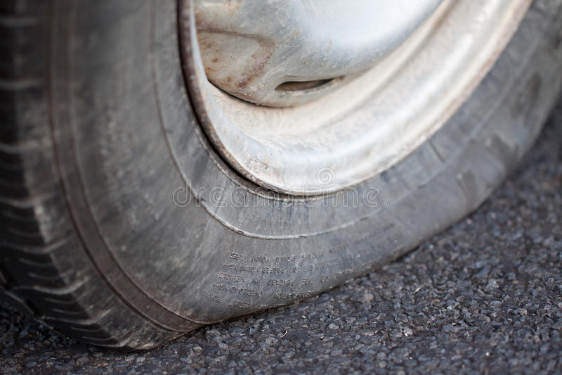 Closeup of a flat tire. A closeup shot of a flat tire of a car royalty free stock photo