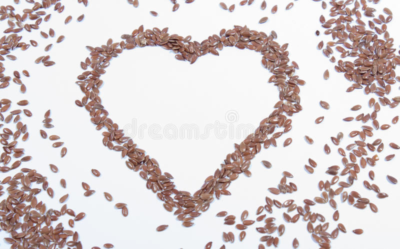 Closeup of flaxseed isolated on white. Flaxseed on white background with a wooden spoon stock images