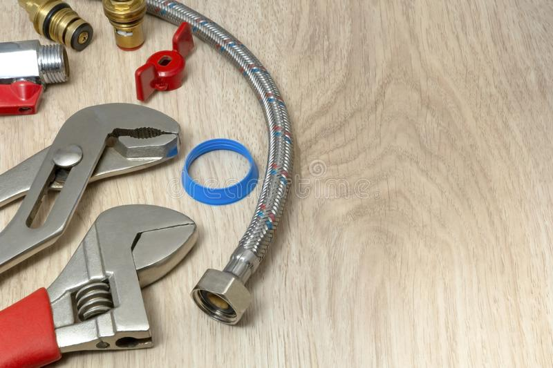 Closeup on flexible water supply tubes and adjustable wrench on wooden background. Suitable for header or banner royalty free stock photography