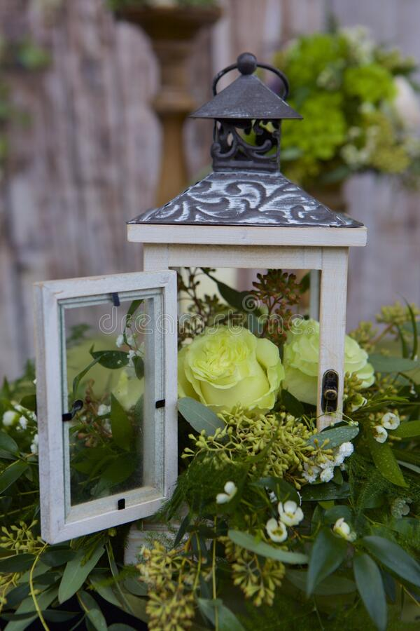 Rose in a Cupola. Closeup of a floral centerpiece in green tones.  Miniature cupola, glass door open to a lime-tinted, newly opened rose.  Fresh, clean, inviting stock images