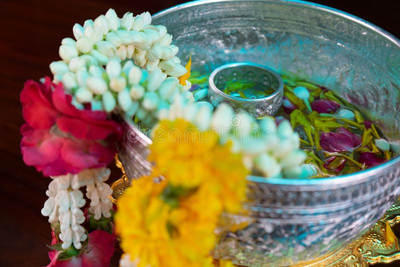 Closeup flower garlands hanging on the edge of silver bowl with flower petal floating on the water in background stock image