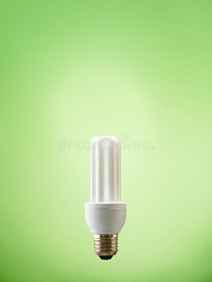 Closeup of fluorescent light bulb. Fluorescent lightbulb on green background. Vertical shape, copy space royalty free stock photography