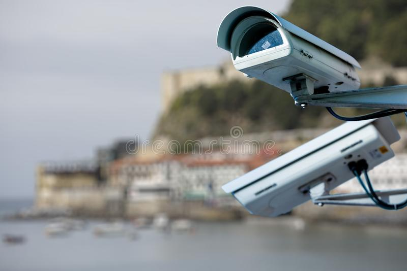 Focus on security CCTV camera or surveillance system with beach on blurry background royalty free stock photography