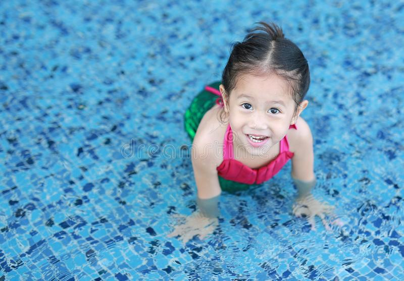 Closeup foot of little child girl wear mermaid swimming suit lying in the pool.  royalty free stock image