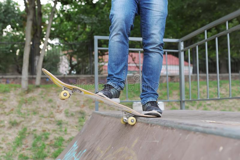 Closeup of foot sneakers and jeans of a skateboarder before the race stock image